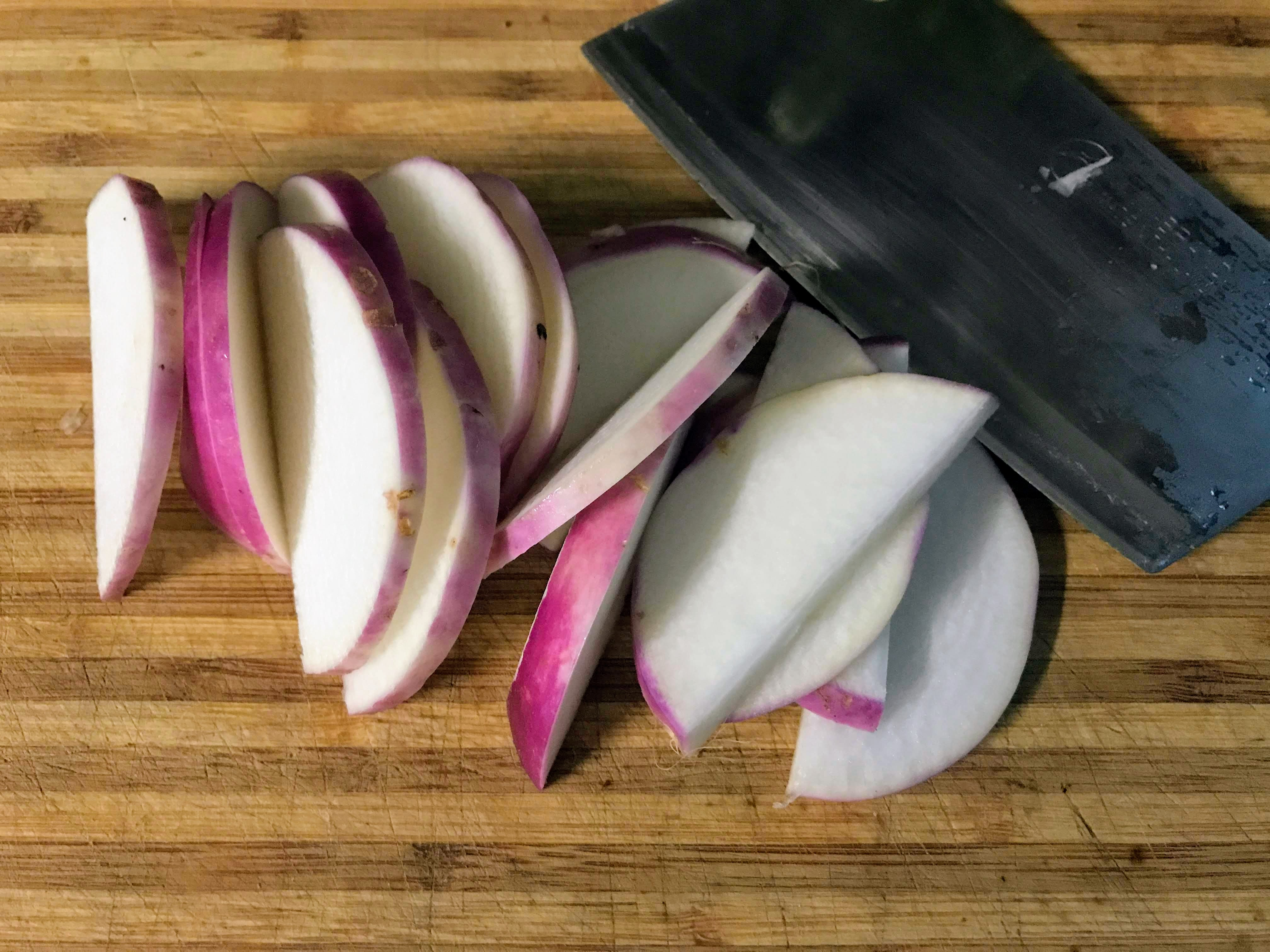 slice turnips on cutting board with knife